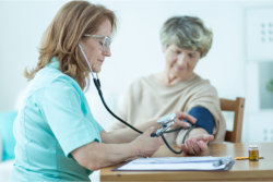 nurse checking the blood pressure of an elder